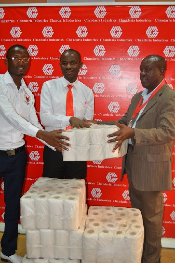 HR Manager Joash Mbulika hands over the bales of tissue to Joseph Ng'anga, Director Heart of Passion Foundation